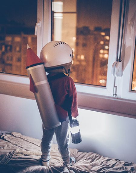 Boy wearing a rocket and standing on the bed and wishing to go to space