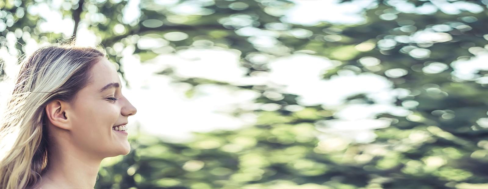 Abgebildet ist eine Frau die lächelt. Im Hintergrund sind Blätter von Bäumen zu sehen.
