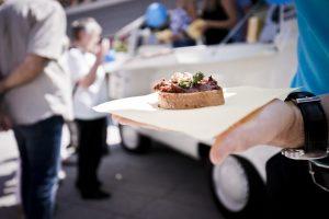 Im Fokus ist eine Hand zu sehen, die eine Baguette Scheibe, bestrichen mit einem Tomate-Walnuss-Aufstrich in der Hand hält. Im Hintergrund sind Menschen.