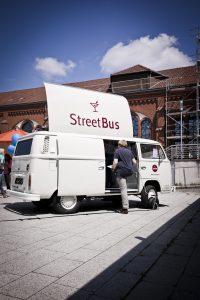 """Abgebildet ist der Bethel Platz in Bielefeld auf dem ein """"Street Bus"""" steht, in den ein Mann einsteigt."""