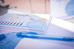 Abgebildet sind Postkarten der BKK diakonie die auf einem Tisch liegen. Im Vordergrund liegen Kugelschreiber der BKK Diakonie