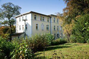 Zu sehen ist das gelbe Hauptgebäude der BKK Diakonie im Königsweg 8 in Bielefeld. Rundherum sind Bäume zu sehen.