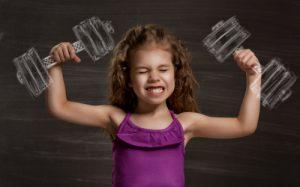 Kleines braunhaariges Mädchen vor einer schwarzen Tafel, angestrengt mit gezeichneten Hanteln in der Hand.