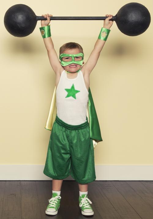 Kleiner Junge in einem grünen Superhelden-Kostüm, der seine Arme nach oben streckt und Gewichte stemmt.