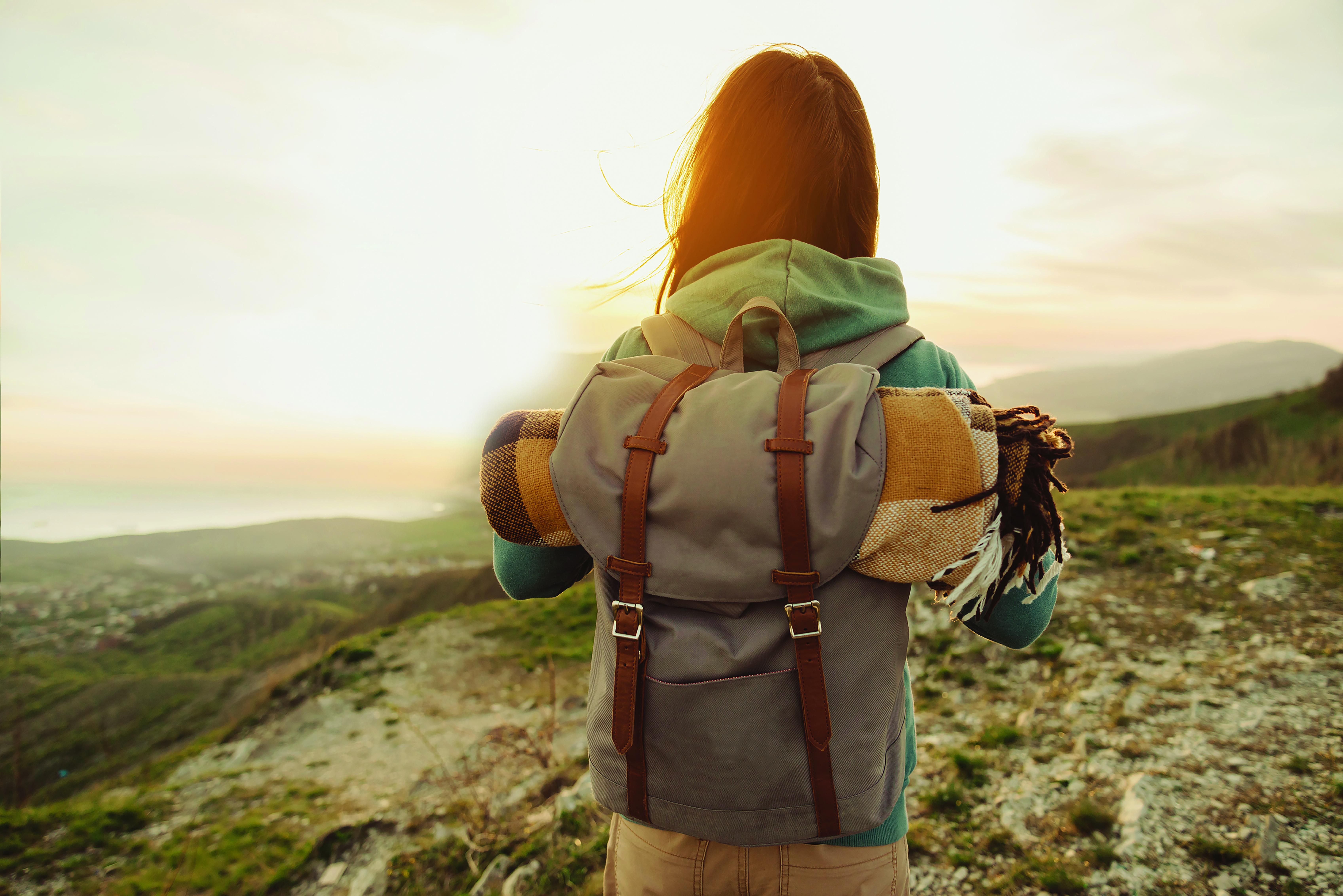 Eine Frau die mit einem Rucksack auf dem Rücken in der Sonne steht und wandert.