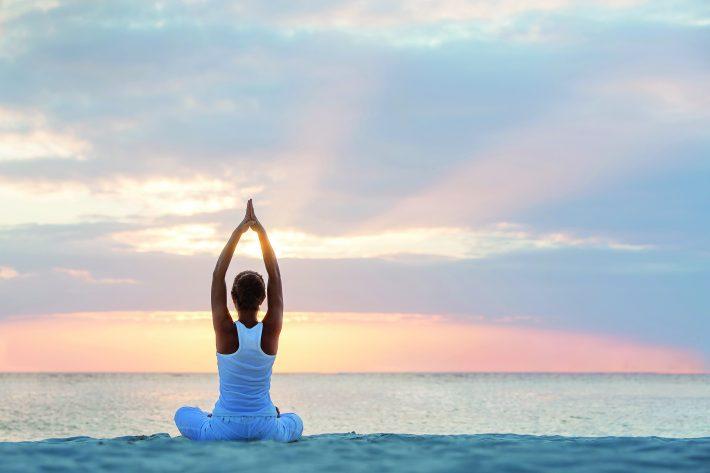 Eine Frau sitzt vor dem Meer und hat eine Yoga Pose eingenommen mit den Armen nach oben. Die Sonne geht auf.