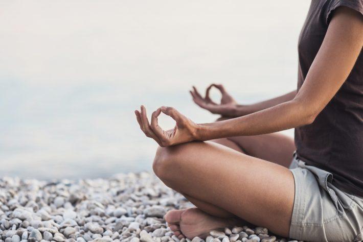 Eine Frau, die an einem Steinstrand sitzt und meditiert.