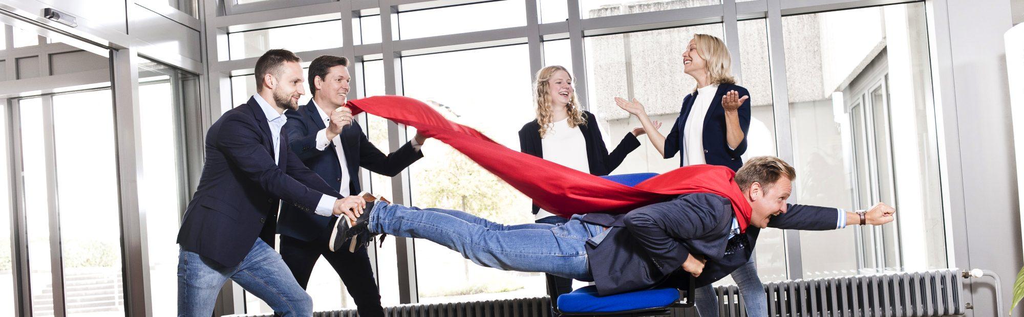 Abgebildet sind fünf Personen die lachen. Im Fokus liegt ein Mann auf einem Stuhl in einem Supermann Kostüm.