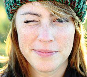 Zu sehen ist der Kopf einer jungen Frau. Ein Auge hat sie zugekniffen. Außerdem trägt sie eine grüne Mütze.
