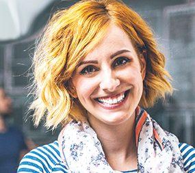 Zu sehen ist der Kopf einer Frau mit rötlichem Haar. Sie lacht.
