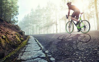 Rennradfahrer der durch an einer Waldstraße entlang fährt und einen Helm trägt. Die Sonne scheint