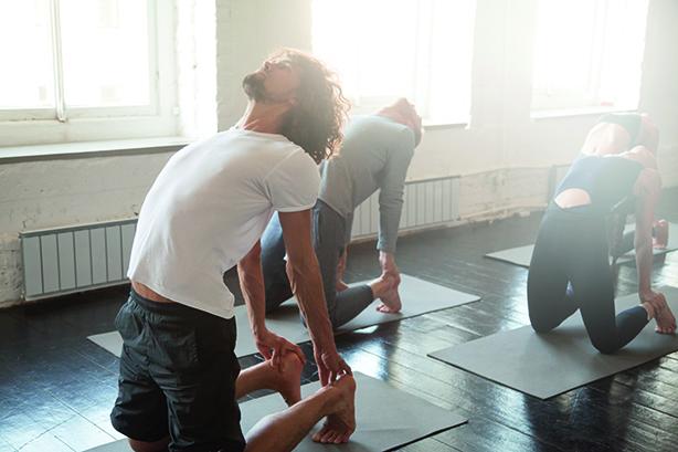 Gruppe junger, sportlicher Menschen die sich in einer Yoga Pose befinden.