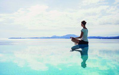 Eine junge Frau, die an einem Pool sitzt und meditiert. Im Hintergrund ist Wasser und ein Berg.