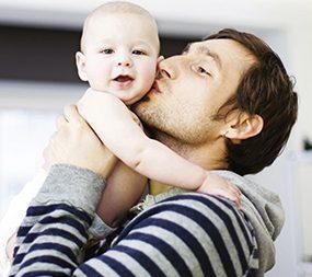 Zu sehen ist ein Mann der ein Kind in den Armen hält und dieses auf die Wange küsst.