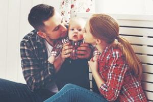 Zu sehen sind Eltern, die ihr Baby auf die Wangen küssen. Sie sitzen vor einem weißen Hintergrund.