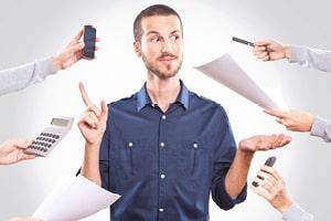 Zu sehen ist ein Mann in dunkelblauem Hemd, sein Blick ist skeptisch. Die eine Hand hält er offen, die andere mit erhobenem Zeigefinger. Verschiedene Hände von außen wollen ihm Sachen anreichen.