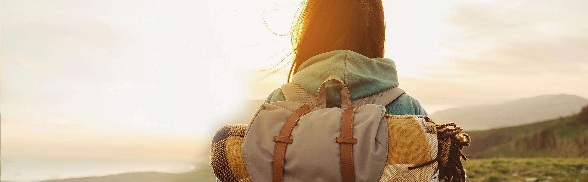 Zu sehen ist der Oberkörper einer Frau von hinten. Sie hat einen Rucksack auf und blickt in die Ferne. Die Sonne scheint ihr entgegen.