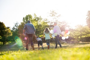 Zu sehen ist eine Familie, Eltern und zwei Kinder. Sie laufen Hand in Hand durch die Natur und die Mutter hält Luftballons.