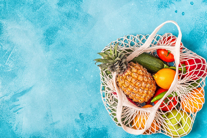 Blauer Hintergrund mit einem Netz-Beutel, der sich unten rechts befindet und gefüllt ist mit frischem Obst und Gemüse. Darunter eine Ananas, Zitronen, Äpfel, Tomaten und Zucchinis.