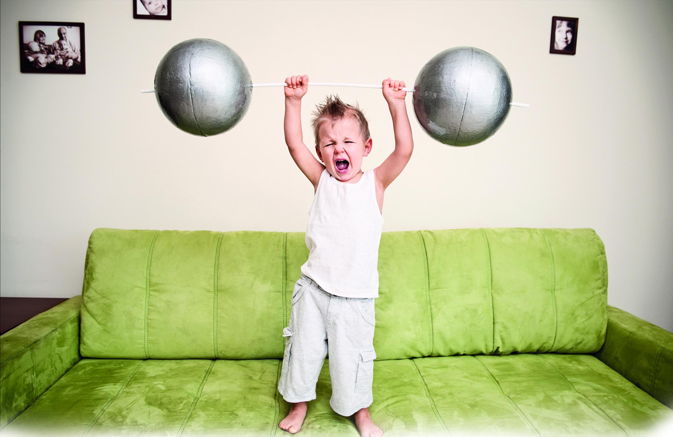 Abgebildet ist ein kleiner Junge auf einem Sofa. Er hält eine Stange mit Gewichten in den Händen.