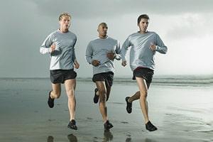 Zu sehen sind drei männliche Läufer, die am Strand entlanglaufen