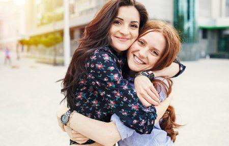 Zu sehen sind zwei junge Frauen, die sich fest umarmen und in die Kamera lächeln.