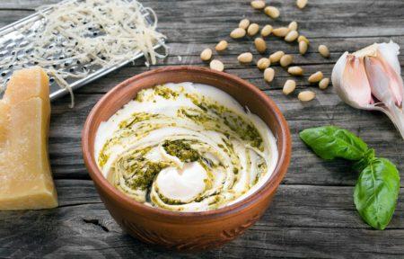 Im Fokus dieses Bildes steht eine Schale selbstgemachtes Pesto auf einem Holztisch. Um das Schälchen herum liegt Parmesan, Pinienkerne, Knoblauch und Basilikum.
