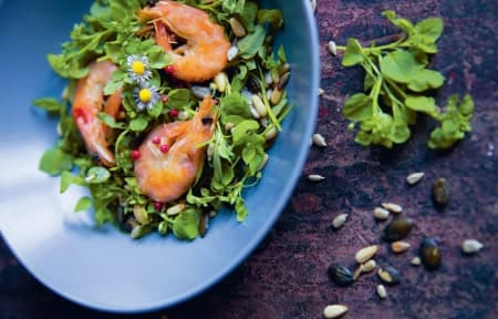 Ein Salat mit Garnelen und Nüssen in einer blauen Schale auf einem schwarzen Hintergrund.