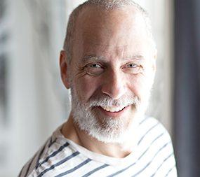Zu sehen ist der Kopf eines älteren Mannes. Er hat einen grauen Bart und lacht.