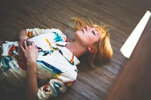 Zu sehen ist eine Frau die mit geschlossenen Augen auf dem Holzboden liegt. Ihre Augen sind geschlossen und die Hände liegen auf ihrem Bauch. Die Sonne scheint in den Raum.