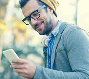 Zu sehen ist ein junger Student. Er trägt eine Brille und eine Mütze. Er blickt lächelnd auf sein Handy.