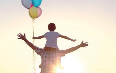 Zu sehen ist ein Mann der ein Kind auf den Schultern trägt. Beide breiten ihre Arme zur Seite aus und gucken in die Sonne. Das Kind hält mehrere bunte Luftballons in der Hand. Sie stehen auf einem Feld.