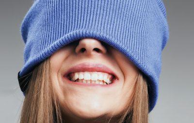 Zu sehen ist der Kopf einer jungen Frau, sie zeigt ihr strahlendes Lächeln. Sie hat eine blaue Mütze auf, welche über ihre Augen gezogen ist.